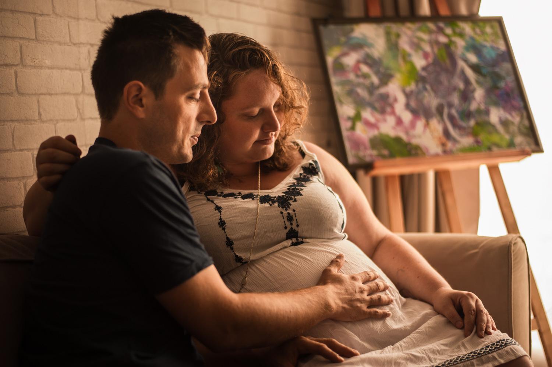 un homme et une femme enceinte assis sur leur canapé le futur papa pose sa main sur le ventre de la future maman