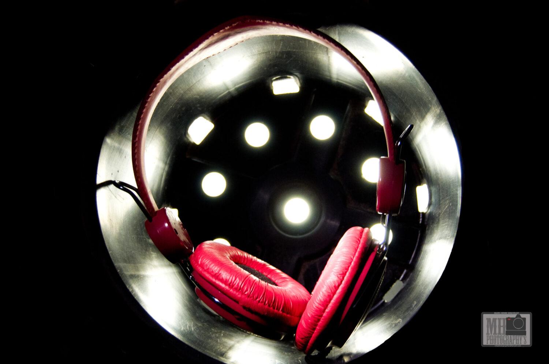casque audio rouge dans un pot de fleur en plastique noir éclairé par une lampe à travers les trous du pot