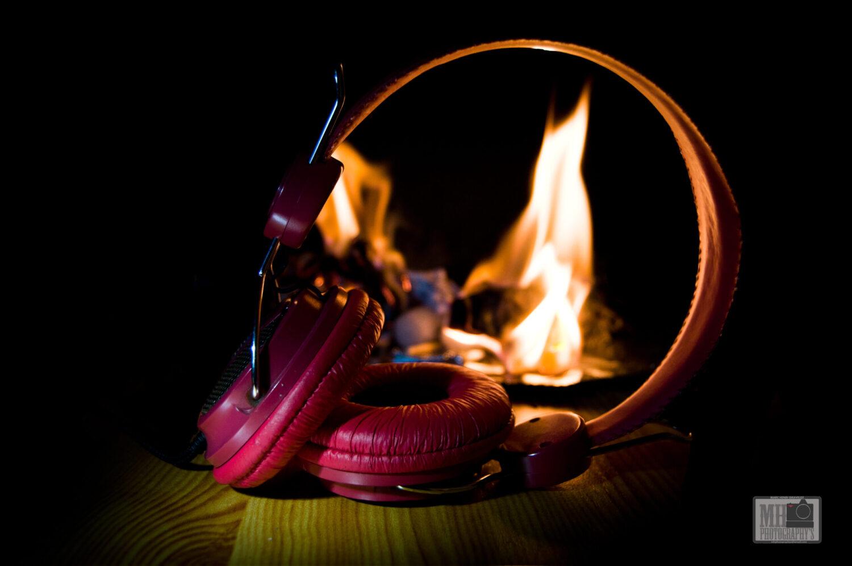 casque audio posé sur une planche de bois avec du feu en arrière plan