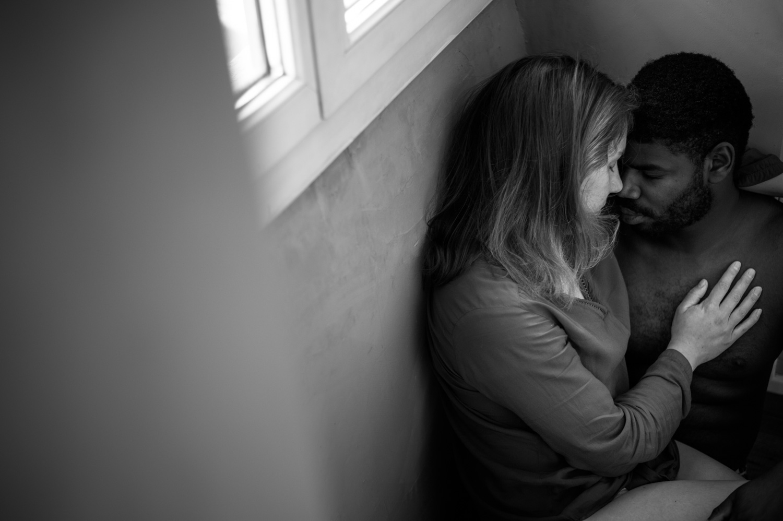 couple assis par terre sous la fenêtre de leur chambre à pau