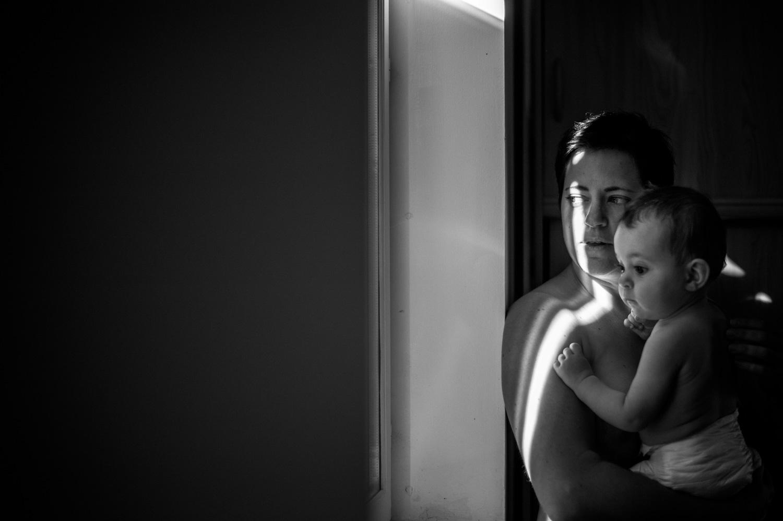 femme torse nu qui porte son bébé contre elle en regardant par la fenêtre