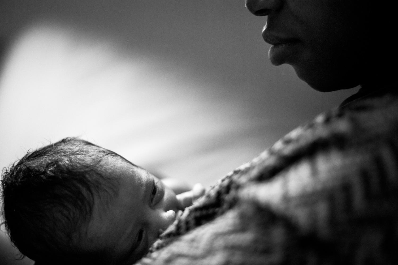 nouveau né qui tète on aperçois qu'une partie du visage de la maman qui la regarde tendrement