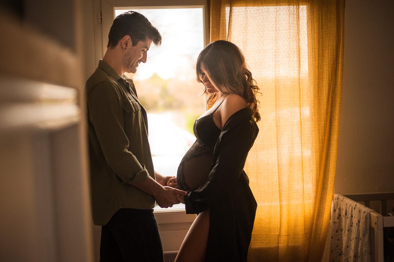 un homme tient les deux mains de sa femme enceinte en face de lui derrière on voit un rideaux jaune qui réchauffe l'ambiance de la photo