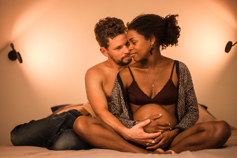 couple assis en tailleur sur leur lit la femme est enceinte ils posent tous les deux leurs mains sur son ventre l'arrière plan est éclairé par deux lampes de chevet murales
