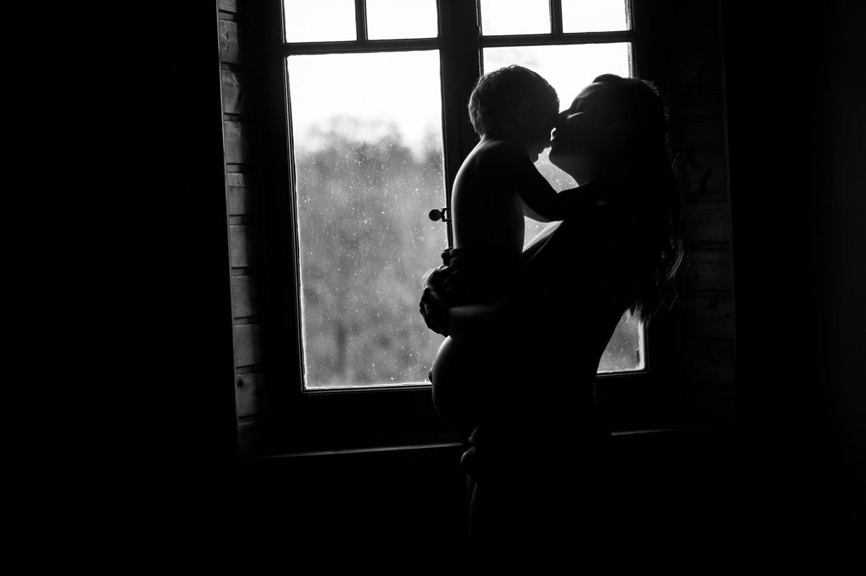 femme enceinte en contre jour devant une fenêtre qui porte son filète lui fait un bisou sur la joue