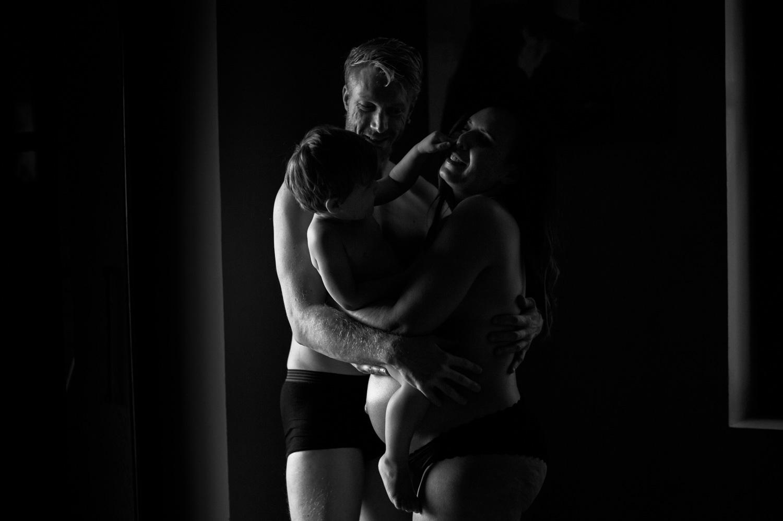 famille composé du papa de la femme qui est enceinte et d'un petit garçon debout dans les bras l'un de l'autre leur silhouette est subtilement éclairé par un filet de lumière de chaque coté